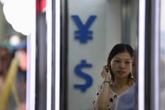 """Una mujer en una casa de cambios en Shanghái, ago 14, 2015. Los recientes flujos transfronterizos de capital de China son """"normales"""" y no son una señal de pánico, afirmó el jueves un alto funcionario del regulador del mercado cambiario, minimizando el temor a un aumento de la tendencia mientras se desacelera la economía.  REUTERS/Aly Song"""