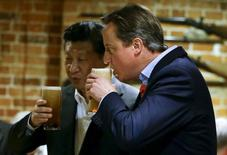 Britain's Prime Minister David Cameron (R) drinks a pint of beer with Chinese President Xi Jinping at a pub in Princess Risborough near Chequers, England, October 22, 2015. REUTERS/Kirsty Wigglesworth/Pool
