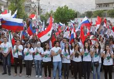 Supporters of Syrian President Bashar al-Assad attend a celebration, organised for Russian President Vladimir Putin after he was sworn in as president on Monday, in front of the Russian embassy in Damascus May 7, 2012. REUTERS/Khaled al- Hariri