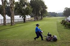 A course worker cuts the grass at a golf club in Hong Kong, China October 22, 2015. REUTERS/Tyrone Siu