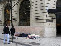 Unas personas pasan frente a una sucursal del Banco Nación mientras otras duermen a las afueras del edificio en Buenos Aires, jun 9, 2015. El desempleo urbano en América Latina y el Caribe subirá hasta un 6,6 por ciento en 2015, por encima de lo registrado el año pasado, debido a los efectos de la desaceleración económica en la región, reveló el martes un informe de la CEPAL y la OIT.   REUTERS/Enrique Marcarian
