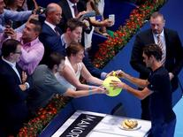 Switzerland's Roger Federer signs a ball after winning against Mikhail Kukushkin of Kazakhstan after their match at the Swiss Indoors ATP men's tennis tournament in Basel, Switzerland October 27, 2015.   REUTERS/Arnd Wiegmann