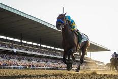Jockey Victor Espinoza, aboard American Pharoah, passes the finish line to win the 147th running of the Belmont Stakes as well as the Triple Crown, in Elmont, New York June 6, 2015.  REUTERS/Lucas Jackson