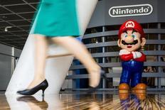 Una mujer pasa junto a Mario Bros, un personaje de uno de los videojuegos de la compañía Nintendo, en una de sus tiendas en Tokio, el 29 de julio de 2015. La compañía japonesa Nintendo Co postergó el jueves el lanzamiento de su servicio de videojuegos para teléfonos inteligentes hasta marzo del 2016, una función muy esperada que fue anunciada por su anterior presidente ejecutivo. REUTERS/Thomas Peter