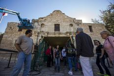 Visitors stand near the entrance as men use a lift to repair and restore stonework along the curved facade of the Alamo in San Antonio, Texas October 26, 2015. REUTERS/Adrees Latif