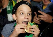 A boy displays the winners' medal given to him by Sonny Bill Williams of New Zealand after the Rugby World Cup Final against Australia at Twickenham in London, October 31, 2015.  REUTERS/Henry Browne