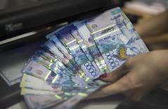 """Сотрудник отделения Евразийского банка в Алма-Ате проверяет подлинность купюр тенге. 15 января 2015 года. Казахстанский госфонд Самрук-Казына не будет заставлять компании, где он владеет долями, конвертировать долларовые сбережения в тенге, сказал в понедельник его глава Умирзак Шукеев и назвал нынешний курс национальной валюты, резко подешевевшей с августа, """"сбалансированным"""". REUTERS/Shamil Zhumatov"""