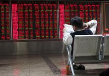 Investidor lendo jornal em frente monitores com cotações, em Pequim.  29/10/2015    REUTERS/Li Sanxian