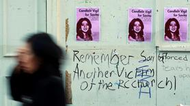 A woman walks past posters advertising a candlelit vigil for a woman who was denied a termination, and later died from septicaemia, at the University Hospital Galway in Galway, in this file photograph dated November 15, 2012. REUTERS/Cathal McNaughton/files
