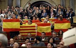 """Депутаты каталонского парламента держат флаги Испании и Каталонии. Барселона, 9 ноября 2015 года. Парламент Каталонии в понедельник одобрил резолюцию об отделении от Испании, запустив, так называемую, """"дорожную карту"""" независимости, которую правительство Испании обещало блокировать. REUTERS/Albert Gea"""
