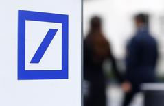 Пешеходы проходят мимо логотипа Deutsche Bank у штаб-квартиры банка во Франкфурте-на-Майне 8 октября 2015 года. Deutsche Bank назначил два управляющих комитета для руководства подразделением по обслуживанию корпоративных клиентов и инвестбанкингу (CIB) и подразделением Global Markets в рамках стратегии смены руководства банка для повышения прибыльности. REUTERS/Ralph Orlowski
