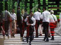Peatones se reflejan en un tablero electrónico que muestra la información bursátil, en Tokio, Japón, 29 de septiembre de 2015. Las bolsas de Asia caían con fuerza el viernes luego de que los precios de las materias primas declinaron a mínimos en varios años, mientras que los funcionarios de la Reserva Federal de Estados Unidos reforzaron el argumento a favor de un alza de las tasas de interés el próximo mes. REUTERS/Issei Kato