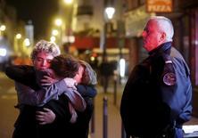 Três pessoas se abraçam perto da casa de shows Bataclan, após uma série de ataques fatais, em Paris, na França, na madrugada de sábado. 14/11/2015 REUTERS/Christian Hartmann