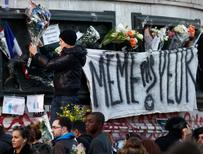 """A man attaches a banner, which translates as """"Don't scare me"""",  to a statue at Place de la Republique near sites of the deadly attacks in Paris, November 15, 2015.    REUTERS/Benoit Tessier"""