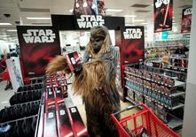 """A fan dressed as Chewbacca selects merchandise from the upcoming film 'Star Wars: The Force Awakens' just before midnight on 'Force Friday' in Sydney, September 4, 2015. New """"Star Wars"""" toys and other merchandise were released in stores across Australia and online around the world just after midnight local time.      REUTERS/Jason Reed"""