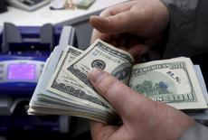 Una persona contando dólares en una casa de cambios en Estambul, abr 15, 2015. El dólar caía el miércoles desde un máximo en siete meses frente a una canasta de divisas, mientras los inversores esperan las minutas de la última reunión de política de la Reserva Federal, que podrían reforzar las expectativas de una subida de las tasas de interés el próximo mes.   REUTERS/Murad Sezer