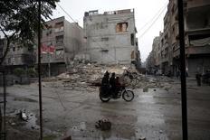 """Жители города Дума, расположенного в Восточной Гуте, едут на мотоцикле. 17 ноября 2015 года. Локальный 15-дневный режим прекращения огня между сирийскими повстанцами и правительственными войсками может быть объявлен в районе Восточная Гута недалеко от Дамаска """"в ближайшие часы"""", сообщила Syrian Observatory for Human Rights в среду. REUTERS/Bassam Khabieh"""