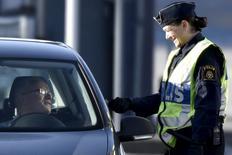 Una agente de la policía pidiendo la identificación a un conductor en Lernacken, en la parte sueca del estrecho de Oresund, el 12 de noviembre de 2015. Los ministros de Interior de la Unión Europea acordarán el viernes intensificar los controles en las fronteras exteriores de la zona Schengen para reforzar la seguridad tras los atentados en París, según un borrador de documento visto por Reuters. REUTERS/Nils Meilvang/Scanpix