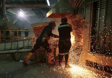 Рабочие в цеху оловоплавильного завода Ausmelt в боливийском городе Винто. 18 сентября 2015 года. Цены на сырьевые товары могут еще раз резко упасть, так как сокращений предложения энергоносителей, металлов и сельскохозяйственной продукции по-прежнему недостаточно в условиях слабого спроса ключевых потребителей, особенно Китая, прогнозирует американский инвестиционный банк Goldman Sachs. REUTERS/David Mercado