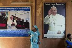 A woman stands in front of posters of Pope Francis at the Martyrs of Uganda church in Bamako, Mali, November 8, 2015. REUTERS/Joe Penney