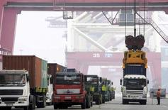 A crane lifts a shipping container from a truck to load it onto a ship at a port in Qingdao, Shandong province, China, October 13, 2015. REUTERS/Stringer