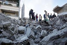 """Жители сирийского города Нава в провинции Дераа осматривают руины здания после авиаобстрела, совершенного, по словам активистов, российской авиацией. 21 ноября 2015 года. Сирийская армия и союзники, при поддержке российских бомбардировок, установили контроль над двумя городами на западе Сирии после тяжелых боев с боевиками """"Исламского государства"""", сообщила группа мониторинга Syrian Observatory for Human Rights в понедельник. REUTERS/Alaa Al-Faqir"""