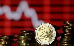 Монеты евро на фоне рыночного графика. Зеница, 30 июня 2015 года. Евро незначительно стабилизировался в начале торгов в Европе в понедельник после падения до минимума более чем за семь месяцев на азиатской сессии, поскольку трейдеры отразили первую атаку на отметку $1,0600. REUTERS/Dado Ruvic