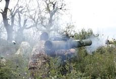 Сирийский боевик стреляет противотанковой ракетой по войскам Башара Асада в районе Джабаль аль-Акрад в провинции Латакия. 25 ноября 2014 года. Сирийские боевики уничтожили во вторник российский вертолет выстрелом ракеты, вскоре после того как вынудили его совершить экстренную посадку в провинции Латакия, контролируемой правительством Сирии, сообщила во вторник мониторинговая группа Syrian Observatory for Human Rights. REUTERS/Alaa Khweled
