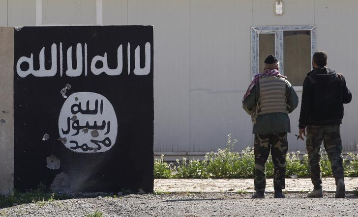 Shi'ite fighters stand near a wall painted with the black flag commonly used by Islamic State militants in the town of Tal Ksaiba, near the town of al-Alam March 7, 2015.   REUTERS/Thaier Al-Sudani