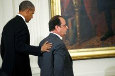 U.S. President Barack Obama (L) pats France's President Francois Hollande on the back as they depart after a joint news conference in the East Room of the White House in Washington November 24, 2015. REUTERS/Carlos Barria - RTX1VNV8