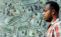 Мужчина проходит мимо рекламы пункта обмена валюты в Каире. 19 ноября 2015 года. Доллар показал существенное падение в среду утром, после того как инвесторы стали закрывать длинные позиции в преддверии Дня благодарения, а также из-за геополитической напряжённости после того, как Турция сбила российский бомбардировщик. REUTERS/Mohamed Abd El Ghany