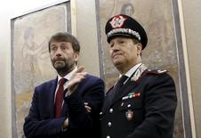 Italy's Culture Minister Dario Franceschini (L) gestures as he stands in front of the parts of a tomb of the hero of Poseidonia and Paestum recovered by the Italian Carabinieri in Rome November 26, 2015. REUTERS/Alessandro Bianchi