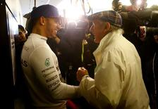 Mercedes Formula One driver Lewis Hamilton of Britain (L) chats with three time retired world champion Jackie Stewart of Britain after Hamilton won the U.S. F1 Grand Prix at the Circuit of The Americas in Austin, Texas October 25, 2015. REUTERS/Mike Stone/Files