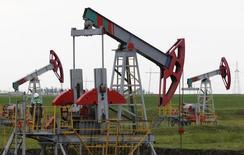 Станки-качалки на месторождении Бузовязовское к северу от Уфы 11 июля 2015 года. Прогноз для российских компаний нефтегазового сектора на 2016 год негативный из-за ожидаемого сохранения низких цен на нефть, повышения налогов, прекращения роста добычи нефти, а также растущего отрицательного эффекта западных санкций, сообщило в понедельник агентство Fitch. REUTERS/Sergei Karpukhin
