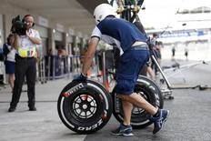 A Williams Formula One crew member pushes tires during the first practice session of the Mexican F1 Grand Prix at Autodromo Hermanos Rodriguez in Mexico City October 30, 2015. REUTERS/Edgard Garrido