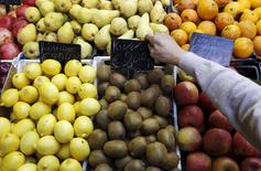 A fruit seller adjusts a price tag in a market in downtown Rome, in this November 14, 2011 file photo. REUTERS/Tony Gentile/Files
