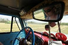 Driver Alexander Belousov, 27, is reflected in the back mirror of a truck transporting grain harvested in a field near the village of Moskovskoye, outside Stavropol in southern Russia, June 26, 2013. Russia and other countries should hold discussions on possible humanitarian deliveries of wheat to Egypt, the world's largest importer of the grain, as it faces an acute shortage, Russia's deputy agriculture minister said. Picture taken June 26, 2013. REUTERS/Eduard Korniyenko (RUSSIA - Tags: AGRICULTURE FOOD POLITICS BUSINESS)