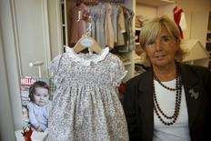 Spanish dressmaker Margarita Pato poses with a dress identical to the one worn by Britain's Princess Charlotte in the latest official photos, at her store in Madrid, Spain, December 5, 2015. REUTERS/Susana Vera