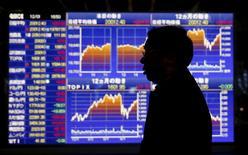 Un hombre camina junto a un tablero electrónico que muestra el índice Nikkei, afuera de una correduría en Tokio, Japón, 1 de diciembre de 2015. Las acciones japonesas rebotaron el lunes luego de que unos datos de empleo optimistas en Estados Unidos sugirieron que la mayor economía del mundo puede resistir un alza de las tasas de interés prevista para este mes. REUTERS/Toru Hanai