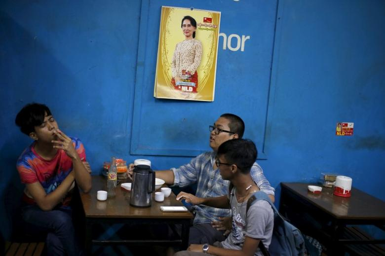 Men sit in a tea house under a calendar with a picture of Myanmar opposition leader Aung San Suu Kyi, in Yangon November 6, 2015. REUTERS/Jorge Silva
