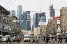 Люди переходят дорогу в Москве на фоне башен Москва-сити 3 апреля 2012 года. Инвестиции в сделки с коммерческой недвижимостью в России на фоне кризиса и оттока капитала снизятся на 32 процента до $3 миллиардов в этому году и могут упасть еще на треть в следующем при сохранении проблем, прогнозирует международный консультант CBRE. REUTERS/Denis Sinyakov