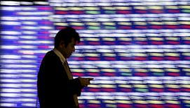 Un hombre camina delante de un tablero electrónico que muestra la información de las acciones, afuera de una correduría en Tokio, Japón, 1 de diciembre de 2015. Las bolsas de Asia caían el miércoles luego de que el desplome de los precios de las materias primas y unos datos que sugieren un enfriamiento de la demanda en China redujeron el apetito de los inversores por los activos de riesgo. REUTERS/Toru Hanai