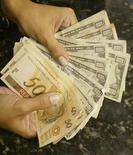 Notas de real e dólar em casa de câmbio no Rio de Janeiro. 07/05/2004 REUTERS/Bruno Domingos