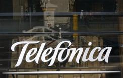 El logo de Telefónica en la fachada de cristal refleja un vehículo circulando por Madrid, el 3 de diciembre de 2012. El grupo español de telecomunicaciones Telefónica anunció el miércoles que lanzará en 2016 servicios de vídeo en siete nuevos mercados latinoamericanos, principalmente bajo la modalidad de ver a pedido y canales de televisión.  REUTERS/Andrea Comas
