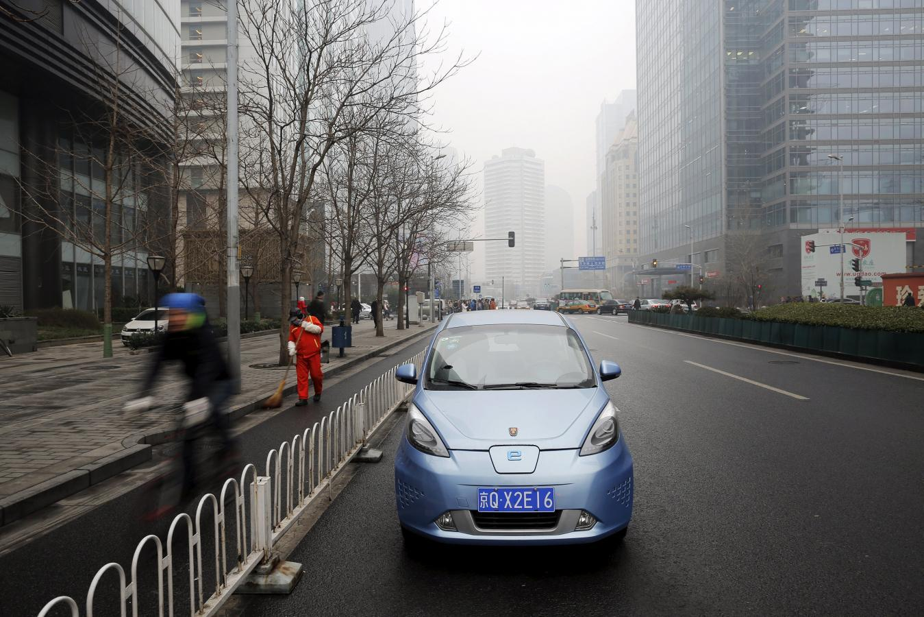 A Roewe E50 Electric Car Is Parked Next To Street As Bicycle Travels Past Amid Heavy Smog After The City Issued Its First Ever Red Alert For Air