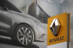 El logo de Renault visto frente a un cartel que promociona una publicidad en una automotora en París, 13 de noviembre de 2015. Renault anunció el viernes un acuerdo con su socio japonés Nissan y el Gobierno francés para poner fin a una disputa de ocho meses sobre el aumento de la influencia estatal en la alianza automotriz. REUTERS/Christian Hartmann