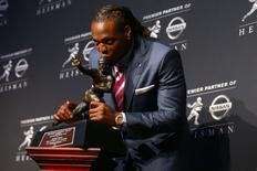 Dec 12, 2015; New York, NY, USA; Alabama running back Derrick Henry kisses the Heisman Trophy during a press conference at the New York Marriott Marquis after winning the trophy during the 81st annual Heisman Trophy presentation. Mandatory Credit: Brad Penner-USA TODAY Sports