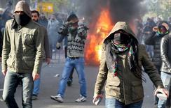 """Демонстранты во время столкновений с полицией в Диярбакыре 14 декабря 2015 года. Турция даст бой курдским повстанцам на охваченном насилием юго-востоке страны, чтобы предотвратить """"распространение пожара"""" из соседних Сирии и Ирака, сказал турецкий премьер-министр Ахмет Давутоглу во вторник. REUTERS/Sertac Kayar"""