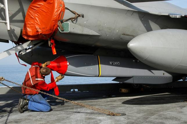An ordnance crew member prepares a 'Scalp' missile on a Rafale fighter jet, to be used for the first time in combat, as France's flagship Charles de Gaulle aircraft carrier continues its mission in the Mediterranean Sea, March 27, 2011. REUTERS/Benoit Tessier