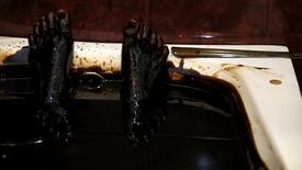 Человек лежит в ванне с нефтью в оздоровительном центре Naftalan в Баку 27 июня 2015 года. Госнефтекомпания Азербайджана пообещала сократить в следующем году расходы из-за падения мировых цен на черное золото, главный источник доходов прикаспийской мусульманской страны. REUTERS/Stoyan Nenov